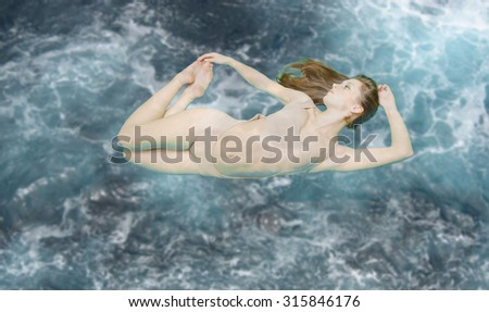 Picture of beautiful young lady floating in light beige swimsuit. Sexi girl bending on blue toned stormy underwater background. Filtered copy space image