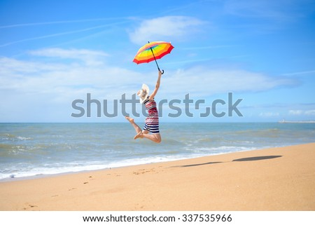 Picture of beautiful young lady holding rainbow umbrella and jumping on golden seashore. Backview of pretty girl having fun on blurred blue sky outdoor background.