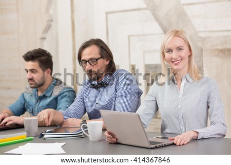 Picture of blond woman looking at camera while working with her colleagues in meeting board. People coworking in office.