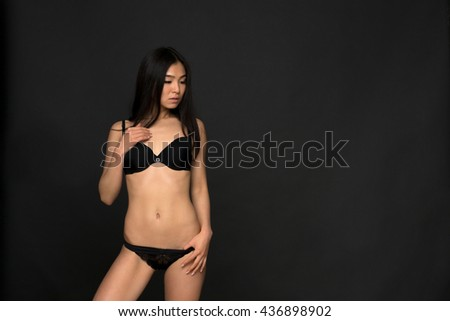 Picture of brunette fashion asian model in black lingerie or underwear in studio. Attractive and gorgeous woman looking down over grey background. - stock photo