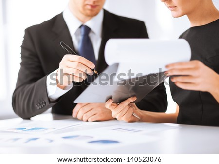picture of businessman and businesswoman signing paper - stock photo