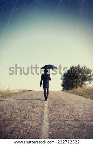 picture of businessman in formal suit walking with black umbrella on empty road against blue sky copy space background - stock photo