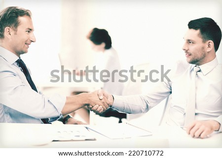 picture of businessmen shaking hands in office - stock photo