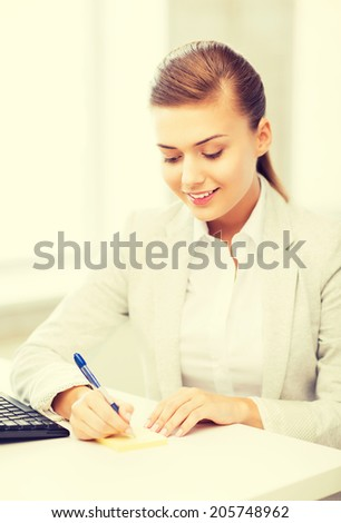 picture of businesswoman writing on sticky note