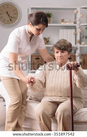 Picture of carer helping senior with walking stick