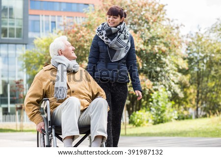 Picture of caring young woman helping her disabled relative - stock photo