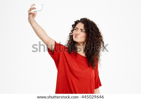 Picture of cheerful curly girl dressed in red t-shirt make selfie over white background - stock photo