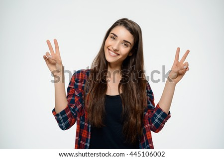 Picture of cheerful girl dressed in plaid shirt make peace gesture. Over white background - stock photo