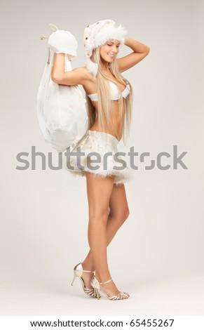 picture of cheerful santa helper girl with big bag - stock photo