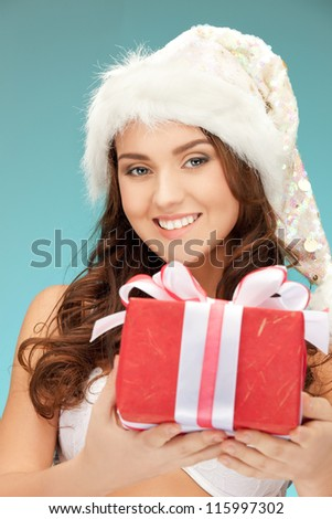 picture of cheerful santa helper girl with gift box... - stock photo