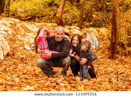 Picture of cheerful young family playing game in autumnal woods, portrait of cute kids with parents in park, autumn holidays, love concept, conceptual of happy family, fall season - stock photo