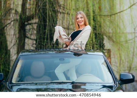 Picture of cheerful young woman wearing sunglasses and raised hands on the sunroof of the luxury car