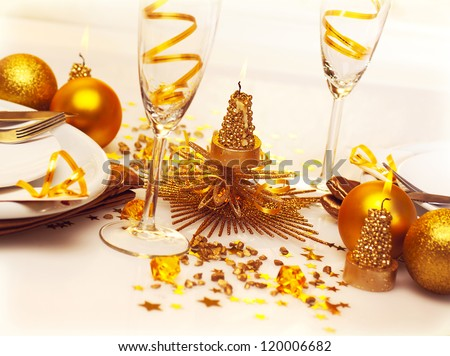 Picture of Christmas romantic table setting, two glasses for champagne adorned with golden ribbon, beautiful little candle, gold shiny bauble, holiday dinner in restaurant, New Year party - stock photo