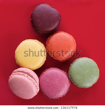 Picture of different colored macaroons on a red background - stock photo
