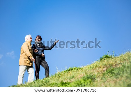 Picture of elderly man relaxing in nature with helpful carer - stock photo
