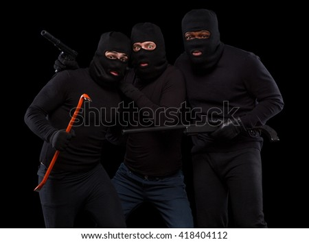Picture of experienced and dangerous thieves in black masks in studio. Men in black balaclavas posing with crowbar, gun, rifle, etc. Isolated on black. - stock photo
