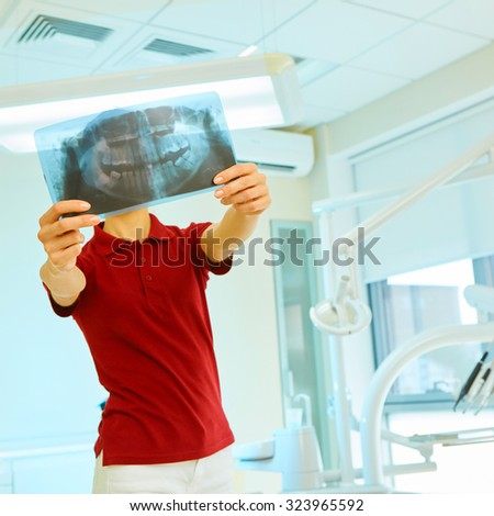 picture of female doctor or dentist looking at x-ray - stock photo