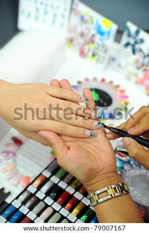 picture of female hands putting a varnish on nails - stock photo