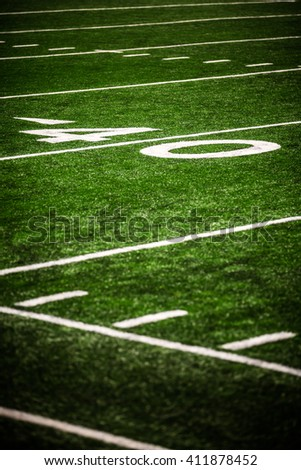 Picture of football field 40 yard line number marker. Photo is vertical, high resolution, has a shallow depth of field, and has copy space for adding text.