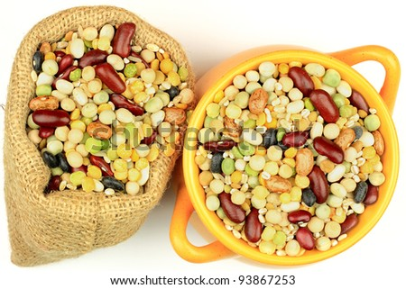 Picture of fourteen premixed beans and seeds (legume, pulse) for cooking soup in orange pottery pot and burlap bag over white background. - stock photo