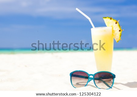 picture of fresh banana and pineapple juice and sunglasses on tropical beach - stock photo