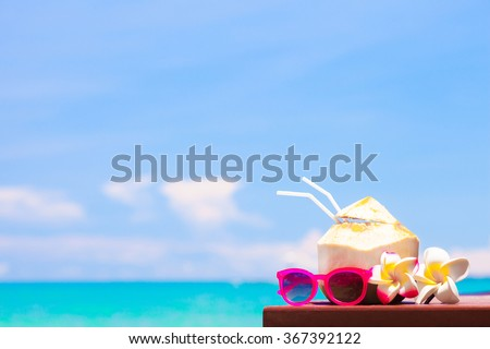 picture of fresh coconut cocktail and pink sunglasses on tropical beach - stock photo