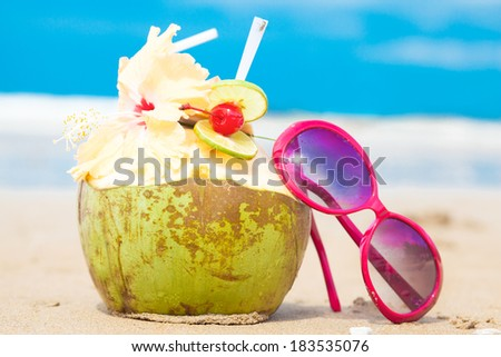 picture of fresh coconut cocktail and red sunglasses on tropical beach - stock photo