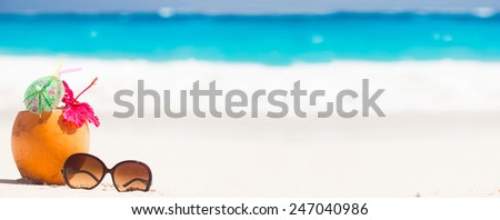 picture of fresh coconut juice and sunglasses on tropical beach - stock photo