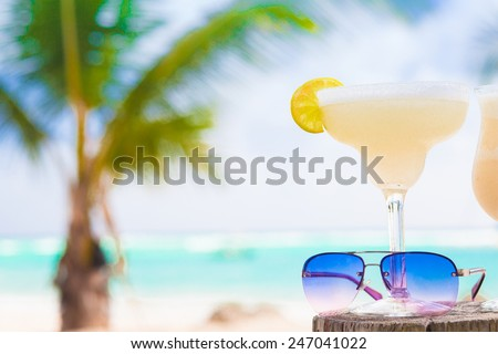 picture of fresh margarita and sunglasses on tropical beach - stock photo