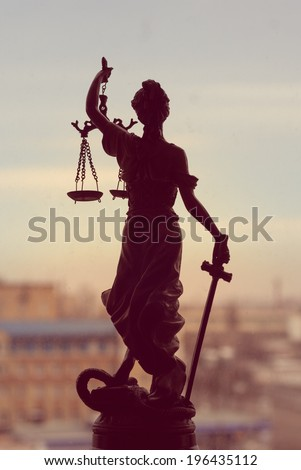 picture of goddess Themis or Lady Justice standing on window holding sword blindfold on the city outdoors background - stock photo