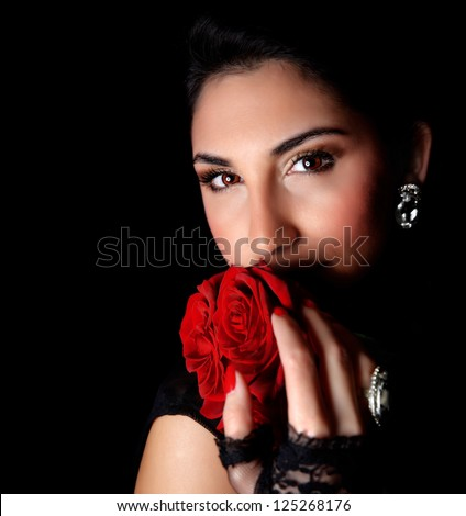 Picture of gorgeous woman holding beautiful red roses in hands isolated on black background, attractive arabic female with bouquet of romantic flowers, Valentines day, love concept - stock photo