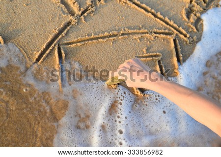 Picture of hand drawing house on sand. Closeup of sketching in surf on sunny seaside background. - stock photo
