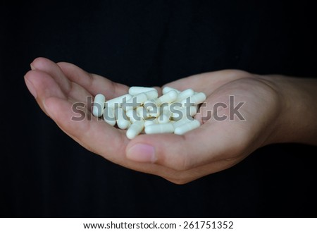 picture of hands holding white pack and pills - stock photo
