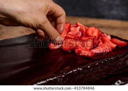 Picture of hands putting strawberry on chocolate pie
