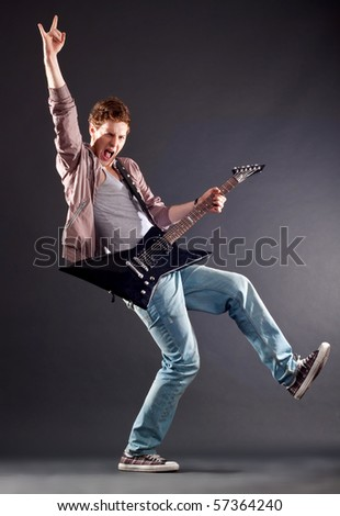 Picture of handsome guitarist making a rock gesture and keeping a leg up - stock photo