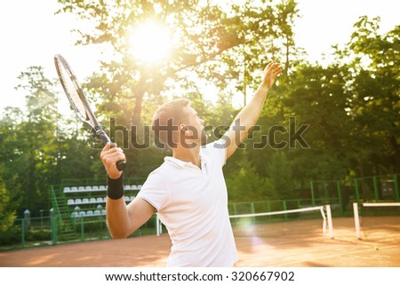Picture of handsome young man on tennis court. Man playing tennis. Man throwing tennis ball. Beautiful forest area as background - stock photo