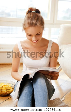 picture of happy and smiling teenage girl with magazine. - stock photo