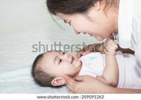Picture of happy asian mother with adorable baby - stock photo
