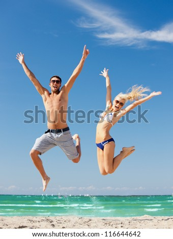 picture of happy couple jumping on the beach (focus on man) - stock photo