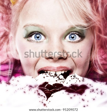 Picture of happy little girl eating cake isolated on pink interior - stock photo