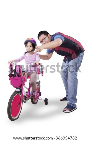 Picture of happy little girl riding bicycle with her father, isolated on white background - stock photo