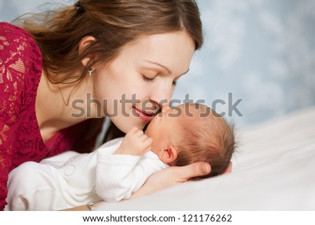 picture of happy mother with baby in bedroom - stock photo