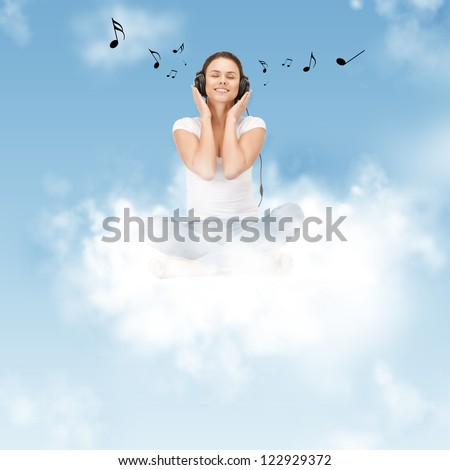 picture of happy teenage girl in big headphones sitting on cloud - stock photo