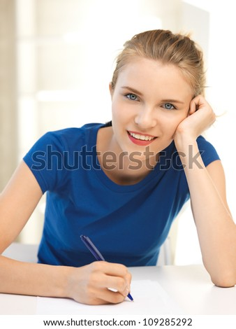 picture of happy teenage girl with pen and paper - stock photo