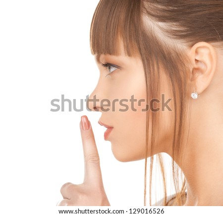 picture of happy woman with finger on lips - stock photo