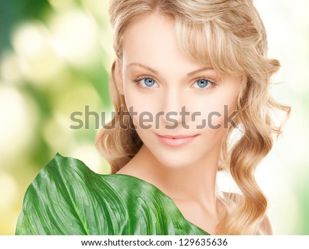 picture of happy woman with green leaf - stock photo