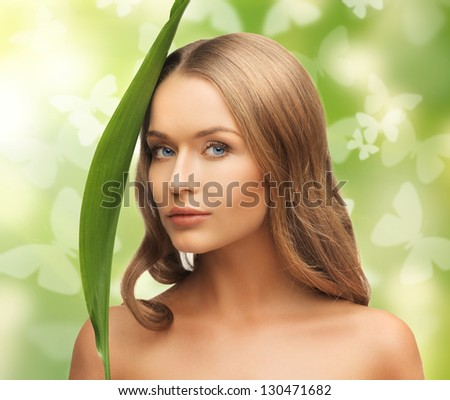picture of happy woman with green leaf and butterflies - stock photo