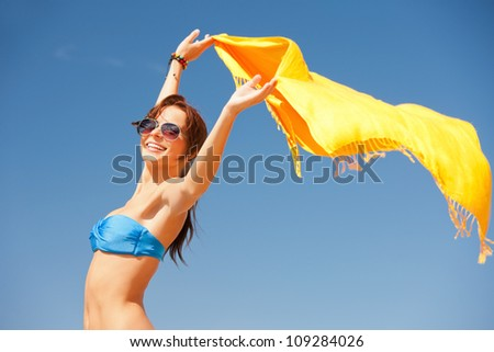 picture of happy woman with yellow sarong on the beach. - stock photo