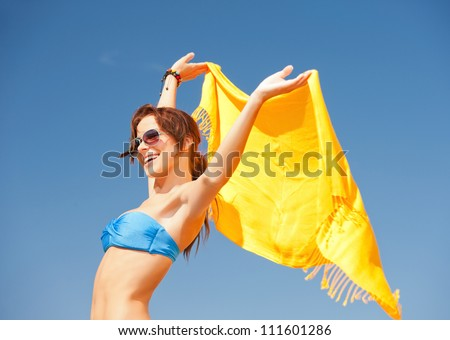 picture of happy woman with yellow sarong on the beach.