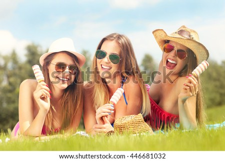 Picture of happy women chilling with ice-cream outdoors - stock photo